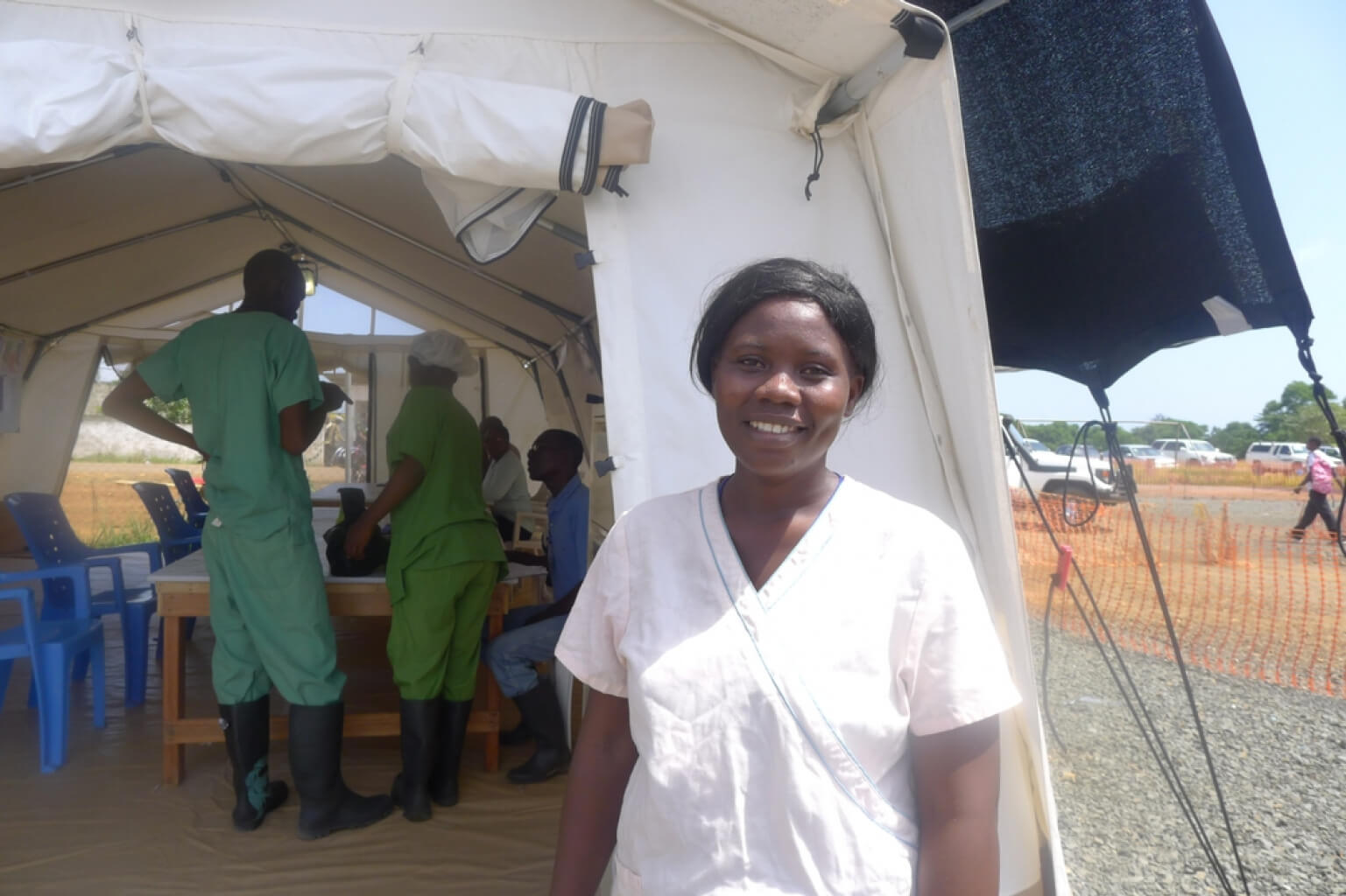 Health Worker in Uniform with Tent of Workers in Background