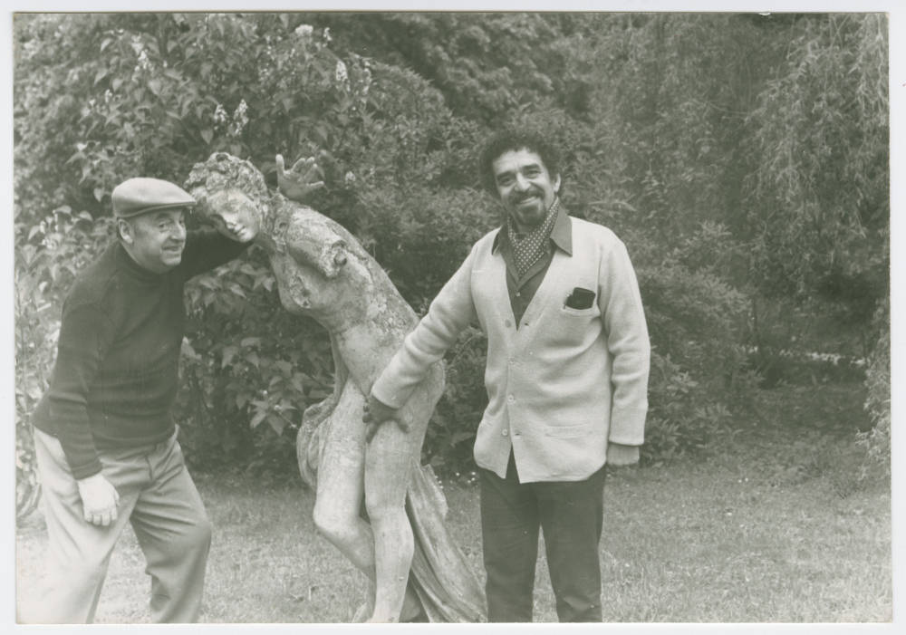 Two Men Posing Around a Statue