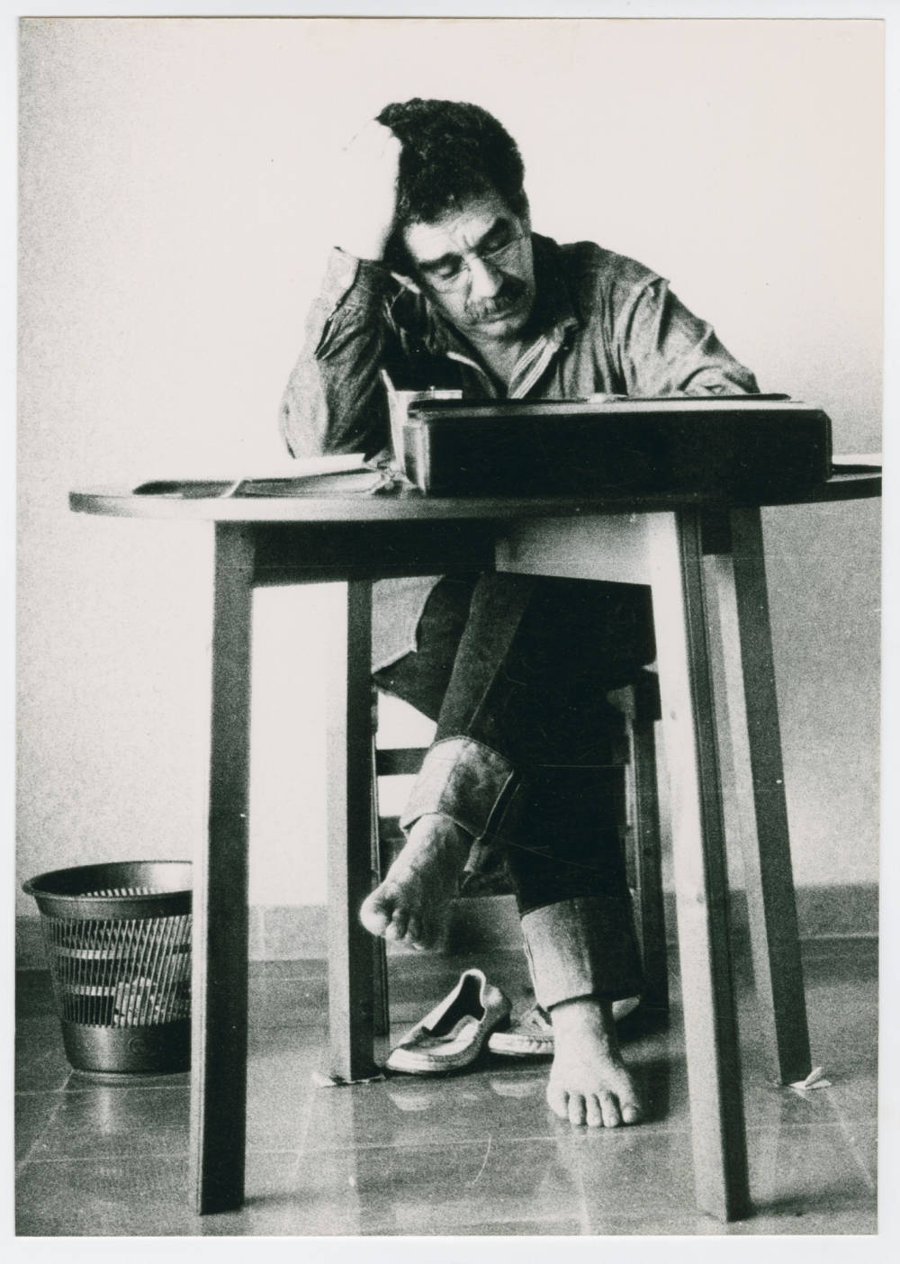 Man Writing At Desk, Head Propped by One Hand