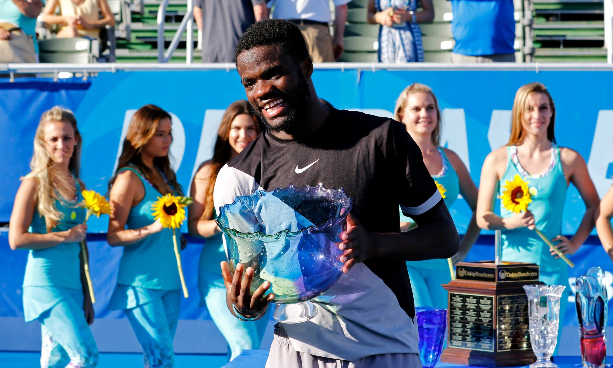 Man Holding Trophy With Tournament Helpers Behind in a Line Holding Flowers