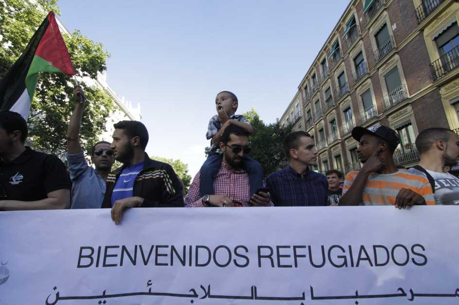 Protesters Holding Banner Welcoming Rufugees