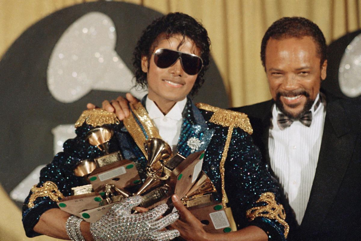 Man Holds Many Awards, Next to Another Man